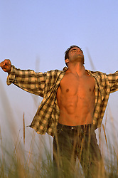 man with an open shirt enjoying the feel of the air on his skin at the beach