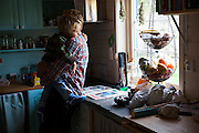 Bjornar Hogset tenderly holds his grandson-in-law Kasper in the kitchen of his home in Sorland, Vaeroy Island, Lofoten Islands, Norway.