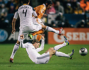 Los Angeles Galaxy midfielder David Beckham, bottom, tackles the ball away from Houston Dynamo forward Calen Carr, top, right, as Galaxy defender Omar Gonzalez covers during the first half of the MLS Cup championship soccer match, Sunday, Nov. 20, 2011, in Carson, Calif. (AP Photo/Bret Hartman)