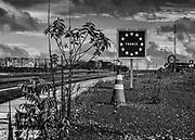 Saint-Georges de l'Oyapock, Guyane, 2015.<br /> <br /> Voie d'accès à la « nouvelle frontière » franco-brésilienne matérialisée par le pont de l'Oyapock. Projet initié en 1997, validé en 2007, lancé en 2008 et terminé en juillet 2011, le pont n'est toujours pas ouvert. Après plusieurs annonces, plus aucune date d'inauguration n'est retenue. Côté brésilien, les travaux de mise en place d'un portail douanier, des accès et de la signalisation sont en cours. La BR-156, la route censée relier le pont au reste du Brésil reste toujours impraticable. Côté français, la route reliant la commune à Cayenne est ouverte depuis 2003, les postes de douanes sont achevées. Une soixantaine de fonctionnaires de la Police aux frontières sont basés aux pieds de l'ouvrage et veillent à ce qu'il ne soit pas utilisé en attendant de pouvoir en assurer le contrôle.<br /> <br /> Pour les personnes, spécificité guyanaise, les Brésiliens n'ont officiellement pas le droit de rentrer sur le territoire guyanais sans visa. Une carte de transfrontalier est en cours de réalisation pour permettre aux riverains brésiliens d'Oiapoque d'emprunter le pont et de se rendre à Saint-Georges pour un séjour n'excédant pas 72 heures.<br /> <br /> Pour les marchandises, les normes françaises et européennes qui s'appliquent bloquent l'entrée d'un certain nombre de produits brésiliens.<br /> <br /> Pour les véhicules, aucune compagnie d'assurance basée en Guyane ne veut prendre en charge un véhicule qui roulerait au Brésil au vu du réseau routier et les poids lourds brésiliens ne pourront pas atteindre Cayenne parce que les ponts en bois de la Route Nationale ne supporte pas tous leur poids.<br /> Sous le pont, les 150 piroguiers qui vivent du transport fluvial continuent à assurer sans discontinuer la traversée pour les enfants brésiliens scolarisés à Saint-Georges, les enseignants français qui habitent sur la rive brésilienne, les brésiliens qui viennent acheter du pain à Saint-Georges et les guyanais qui vont fai
