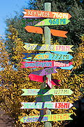 Bright color jokey fun direction signpost with distances for far flung places in Natchez, Mississippi USA
