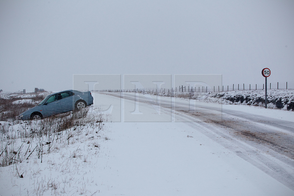 © Licensed to London News Pictures. 27/01/2012. Derbyshire, UK. A car is left abandoned in a ditch at the side of the road after it comes off the road during a severe snowfall. Drivers struggle with the impact of a severe snowfall along Derbyshire's notorious Snake Pass Road. Photo credit : Joel Goodman/LNP