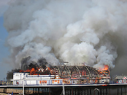 **HIGH RES VERSION** © Licensed to London News Pictures. 30/07/2014. London, UK.  A fire has broken out on Eastbourne Pier this afternoon, 30th July 2014. Firefighters, police, coastguards and lifeboat crews are at the scene after a fire was discovered in a wall panel of an arcade at the front of the Victorian structure. Photo credit : Martin Stott/LNP