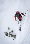A ski patroller telemarks through fresh December powder beneath the Garfield Lift at Monarch Mountain.