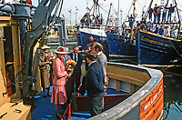 Princess Anne on a May 1985 Royal Visit to N Ireland meets the crew of Willing Lad, a fishing boat in the harbour at Portavogie, Co Down, N Ireland. The crews of other fishing boats get a grandstand view of the visit. Princess Anne had just officially re-opened the harbour after extensive improvements. 19850502f.<br /> <br /> Copyright Image from Victor Patterson, 54 Dorchester Park, Belfast, UK, BT9 6RJ<br /> <br /> t: +44 28 9066 1296 (from Rep of Ireland 048 9066 1296) m: +44 7802 353836 <br /> <br /> victorpattersonbelfast@gmail.com www.victorpatterson.com<br /> <br /> Please see my Terms and Conditions of Use at https://www.victorpatterson.com/page2 It is IMPORTANT that you familiarise yourself with them.<br /> <br /> Images used on the Internet incur an additional cost and must be visibly watermarked i.e. © Victor Patterson within the body of the image and copyright metadata must not be deleted. Images used on the Internet have a size restriction of 4kbs and are chargeable at rates available at victorpatterson.com.<br /> <br /> This image is only available for the use of the download recipient i.e. television station, newspaper, magazine, book publisher, etc, and must not be passed on to any third party. It is also downloaded on condition that each and every usage is notified within 7 days to victorpattersonbelfast@gmail.com<br /> <br /> The right of Victor Patterson to be identified as the author is asserted in accordance with The Copyright Designs And Patents Act (1988).<br /> <br /> All moral rights are asserted.