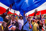 """09 DECEMBER 2013 - BANGKOK, THAILAND: Thai anti-government protestors walk to Government House under a Thai flag in Bangkok. Thai Prime Minister Yingluck Shinawatra announced she would dissolve the lower house of the Parliament and call new elections in the face of ongoing anti-government protests in Bangkok. Hundreds of thousands of people flocked to Government House, the office of the Prime Minister, Monday to celebrate the collapse of the government after Yingluck made her announcement. Former Deputy Prime Minister Suthep Thaugsuban, the organizer of the protests, said the protests would continue until the """"Thaksin influence is uprooted from Thailand."""" There were no reports of violence in the protests Monday.      PHOTO BY JACK KURTZ"""