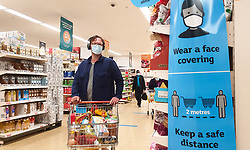 © Licensed to London News Pictures. 12/07/2021. London, UK. A shopper wearing a face covering walks past 'Wear a Face Covering' and 'Keep a safe distance' signs in a Sainsbury's supermarket in London. Prime Minister Boris Johnson will provide an update to step four of easing the Covid-19 lockdown in a press conference later today. It is expected that the face coverings in shops, pubs and mass events will no longer be mandatory after Freedom Day on 19 July. Businesses will be able to set rules for entry to their own premises. Vaccines Minister Nadhim Zahawi said that people will still be expected to wear a face covering in 'enclosed indoor spaces', though it will no longer be legal to do so. Photo credit: Dinendra Haria/LNP