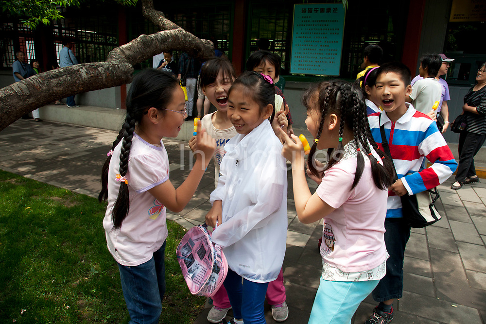 Group of young girls laugh at one of their friends after she makes an amusing error. It is very good natured and the girl laughs at her own mistake, while the rest of them point and can't stop laughing. National Children's Day in Zhongshan Park, Beijing, China. Zhongshan Park is a former imperial garden and now public park that lies in the Dongcheng District of central Beijing. Of all the gardens and parks Zhongshan is arguably the most centrally located of them all and houses numerous pavilions, gardens, and imperial temples.