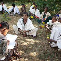 "Women deposit money into a credit union during a weekly meeting of the Serten Endege, a support organization for women from the Agew community in Beshenty, 18km from Bahir Dar. The the meeting allows women deposit money into their credit union and discuss honey production. The Serten Endege was established three months ago among women who use traditional beehives but are looking to move to modern beehives following training from the Zembaba Union. This training motivated them to form the Serten Endege. The Serten Endege are not yet a constituent coop of the Zembaba Union. <br /> <br /> Harvesting honey supplements the income of small farmers in the Ethiopian region of Amhara where there is a long tradition of honey production. However, without the resources to properly invest in production and the continued use of of traditional, low-yielding hives, farmers have not been able to reap proper reward for their labour. <br /> <br /> The formation of the Zembaba Bee Products Development and Marketing Cooperative Union is an attempt to realize the potential of honey production in Amhara and ensure that the benefits reach small producers. <br /> <br /> By providing modern, high-yield hives, protective equipment and training to beekeepers, the Cooperative Union helps increase production and secure a steady supply of honey for which there is growing demand both in and beyond Ethiopia. The collective processing, marketing and distribution of Zembaba's ""Amar"" honey means that profits stay within the cooperative network of 3,500 beekeepers rather than being passed onto brokers and agents. The Union has signed an agreement with the multinational Ambrosia group to supply honey to the export market. <br /> <br /> Zembaba Bee Products Development and Marketing Cooperative Union also provides credit to individual members and trains carpenters in the production of modern hives. <br /> <br /> Photo: Tom Pietrasik<br /> Amhara. Ethiopia<br /> November 16th 2010"