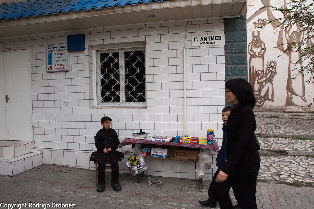 A boy sells cigarettes and snacks on a street corner in Osh (Kyrgyzstan).