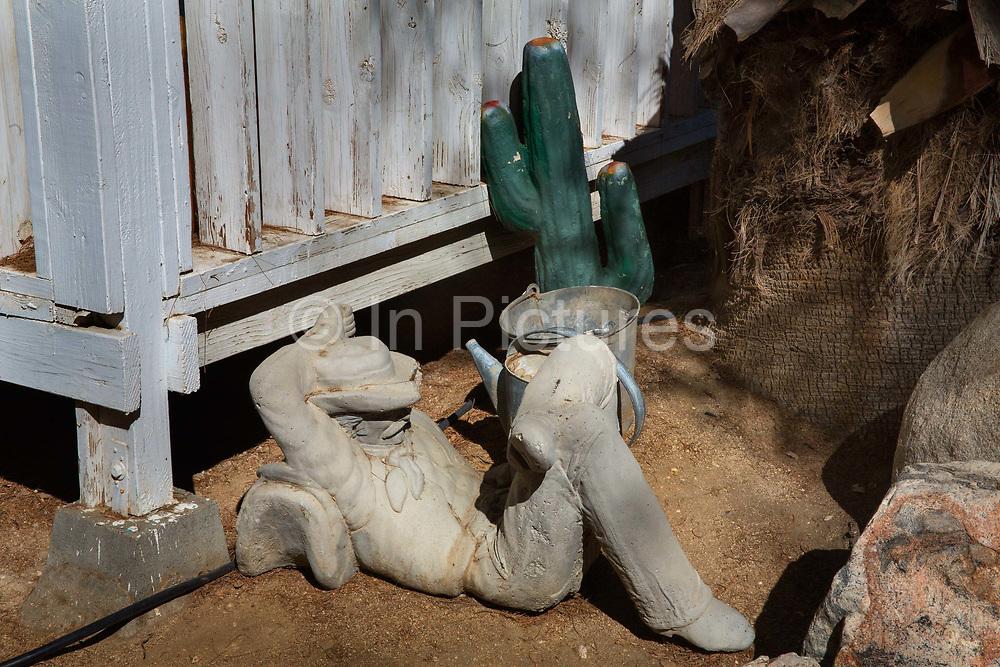 Sleeping concrete cowboy concrete sculpture in the Safari Hotel hot spring spa, Desert Hot Springs