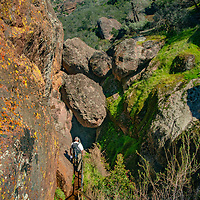 A hiker descends into the Bear Gulch Cave below the Reservoir in Pinnacles National Monument, San Benito County, California.