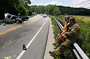 Bloomington firefighter Greg Lucas, foreground, and Capt. Jean Magrane take a moment to rest Thursday while working at the scene of a fatal car accident on Ind. 46 east of Bloomington. (Photo by Jeremy Hogan)