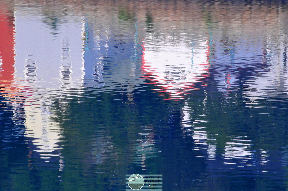 Captured images of water that reflect boats and fishing village buildings.  Colorful compositions create liquid blurred visions of nautical environments.