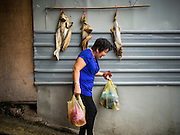 06 OCTOBER 2014 - GEORGE TOWN, PENANG, MALAYSIA: A woman walks out of a market in George Town (also Georgetown), the capital of the state of Penang in Malaysia. Named after Britain's King George III, George Town is located on the north-east corner of Penang Island. The inner city has a population of 720,202 and the metropolitan area known as George Town Conurbation which consists of Penang Island, Seberang Prai, Kulim and Sungai Petani has a combined population of 2,292,394, making it the second largest metropolitan area in Malaysia. The inner city of George Town is a UNESCO World Heritage Site and one of the most popular international tourist destinations in Malaysia.      PHOTO BY JACK KURTZ
