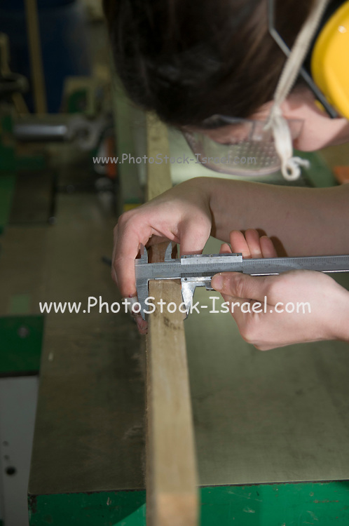 Female carpenter measures the thickness of a plank of wood with a Caliper