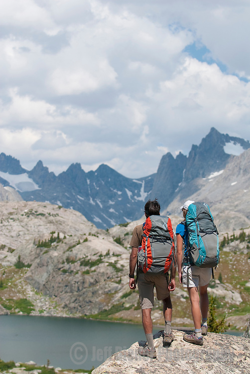 A young couple takes in the view while backpacking above Island Lake in the Wind River Mountains, Wyoming.