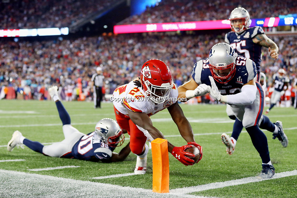 Kareem Hunt #27 of the Kansas City Chiefs dives for the pylon to score a 4-yard rushing touchdown during the fourth quarter against the New England Patriots at Gillette Stadium on September 7, 2017 in Foxboro, Massachusetts.