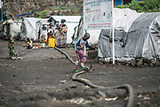 A boy walks on a water pipe while rolling a hoop in Lac Vert IDP camp.