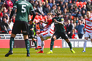 Kieran Sadlier of Doncaster Rovers (22) and Yann Songo'o of Plymouth Argyle (4) in action during the EFL Sky Bet League 1 match between Doncaster Rovers and Plymouth Argyle at the Keepmoat Stadium, Doncaster, England on 13 April 2019.