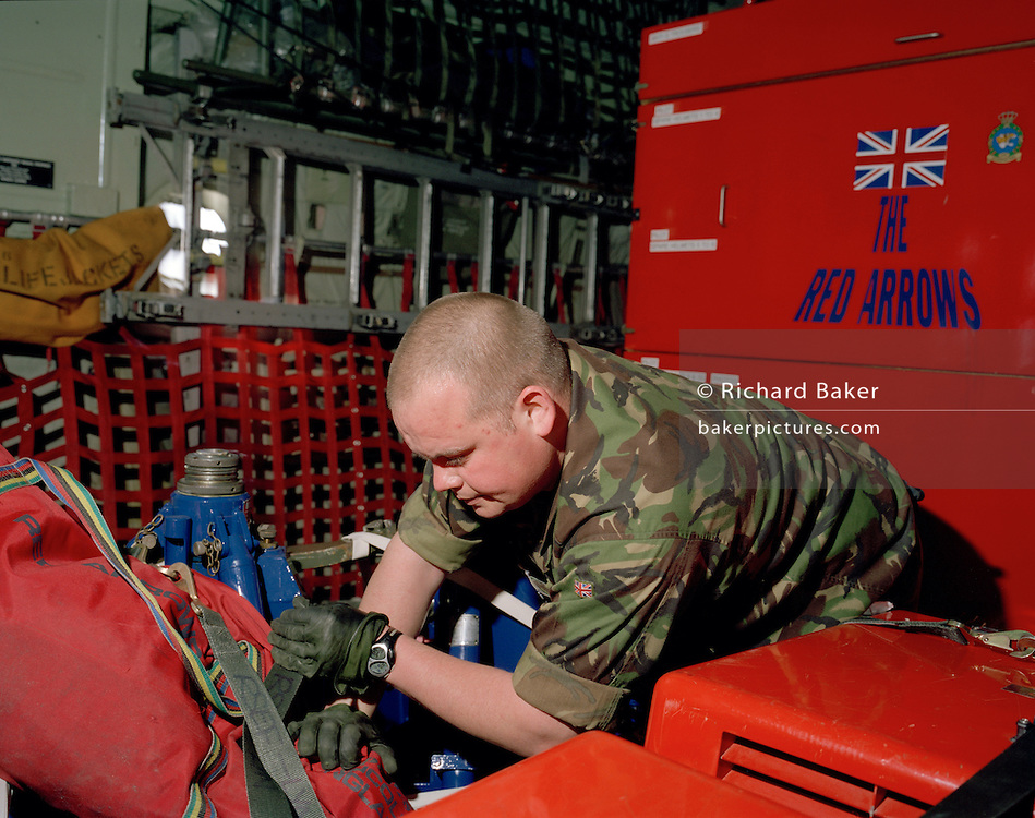 A member of the 'Red Arrows', Britain's Royal Air Force aerobatic team, supervise the loading of spares and personal effects into a C-130 Hercules aircraft before the two-day journey from RAF Scampton to RAF Akrotiri in Cyprus. Surrounded by heavy-duty flight-spares, survival equipment boxes and a tyre for a Hawk jet aircraft, the Hercules looms large in the overcast sky. The team complete their winter training schedule in Cyprus. The Red Arrows pilots fly their own jet aircraft to air shows but when requiring the support of ground crew  they borrow a transporter to fly behind the main airborne squadron. 10 tons of spares and personal effects are shipped for a six-week stay.