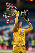Courtois hold up the cup offering to supporters at Santiago Bernebeu Stadium