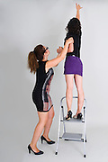 A young woman supports another on a step ladder while she stretches to reach up