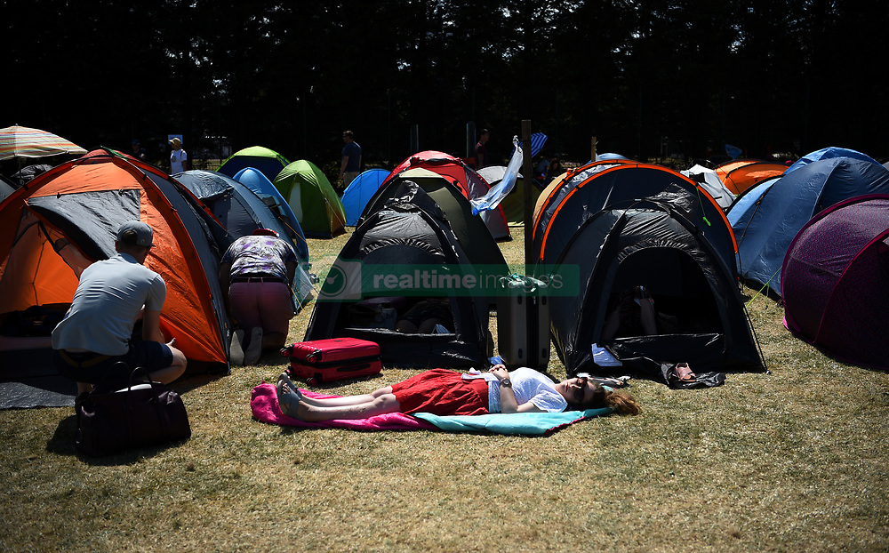 A women snoozes in the queue on day two of the Wimbledon Championships at the All England Lawn Tennis and Croquet Club, Wimbledon.