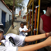 School children ride the Bondinho, tram or trolley car as it heads along the streets of Santa Teresa in the hills of Rio de Janeiro. The trap ride from the City Centre across the Lapa Aquaduct is popular for both tourists and locals. Rio de Janeiro,  Brazil. 20th September 2010. Photo Tim Clayton.