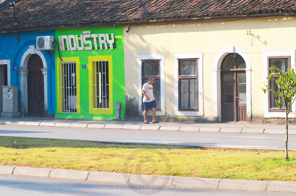 On the boulevard Ivana Cronjevica. Shops in small colourful houses. One shop with a sign saying 'New Industry'. A man walking past. Podgorica capital. Montenegro, Balkan, Europe.