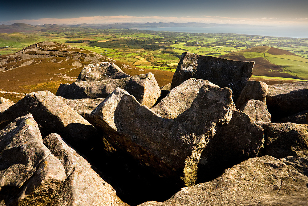The Iron Age hill-fort of Tre'r Ceiri hugs the nearby hill top, as seen from Yr Eifl, with Harlech and Cardigan Bay in the background.