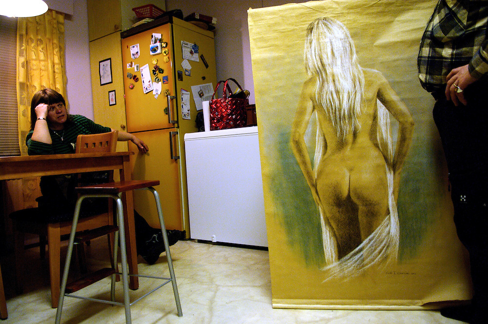 A husband shows off a nude pastel drawing won at a fair to his wife.