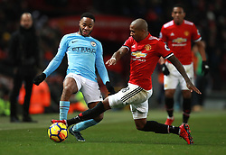 Manchester City's Raheem Sterling (left) and Manchester United's Ashley Young (right) battle for the ball