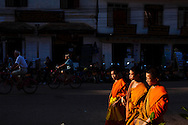 Boys from a Buddhist monastery walk down the street in Luang Prabang, Laos.