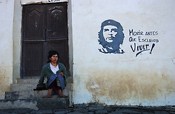 "The image of Che Guevara stands for many things throughout Latin America, from a young traveler to an anti-U.S., anti-imperialist revolutionary.  Here a woman sits on her front porch in La Higuera, the town where Che Guevara was captured and killed.  The words read : ""Death before slavery. Live!, Che Lives""."