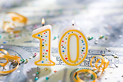 Ten (10) year celebration candle on U.S. currency.