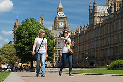 © Licensed to London News Pictures. 19/05/2014. London, UK. Two women walk in the sunshine near Big Ben, Westminster, London on 19th May 2014. Photo credit : Vickie Flores/LNP