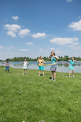 Group of friends spinning plastic hoops at lakeside, Munich, Bavaria, Germany
