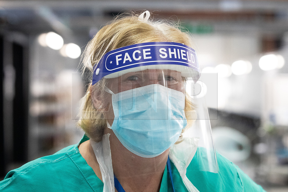 © Licensed to London News Pictures . 15/04/2020. Manchester, UK. A clinician wearing a face shield in the PPE donning area of the hospital . The National Health Service has built a 648 bed field hospital for the treatment of Covid-19 patients , at the historical railway station terminus which now forms the main hall of the Manchester Central Convention Centre . The facility is due to fully open this week (ending Friday 17th April 2020 ) and will treat patients from across the North West of England , providing them with general medical care and oxygen therapy after discharge from Intensive Care Units . Photo credit : Joel Goodman/LNP