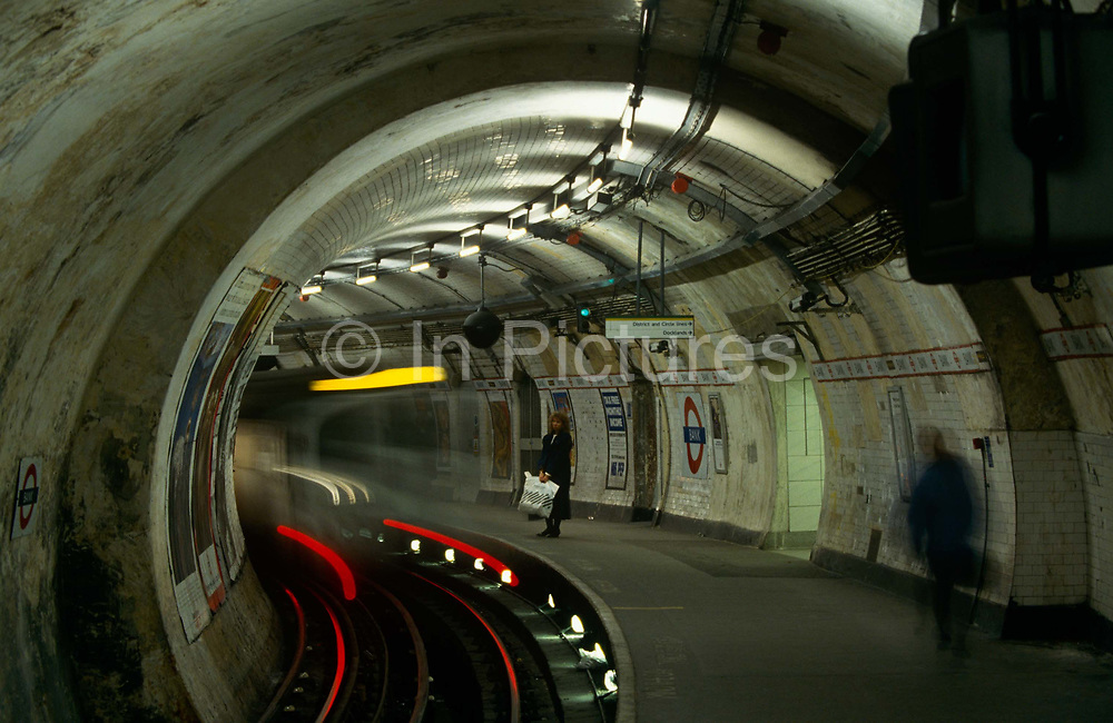 "As a departing train disappears round the corner at Bank underground station in the heart of London's financial district, a lone woman waits for the next service. This is the grim face of 90s tube travel is seen here in a wide landscape of rounded tunnel and the curve of the station platform on the Central Line. The Central line is a London Underground line, coloured red on the tube map. It is a deep-level ""tube"" line, running east-west across London, and, at 76 km (47 mi). Incorporated in 1891 it is today the longest Underground line and also the busiest with around 260 million passengers a year."