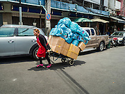 07 JUNE 2016 - BANGKOK, THAILAND: A woman pulls a handtruck of toys down a street in Verng Nakorn Kasem, also known as the Thieves' Market. Verng Nakorn Kasem was one of Bangkok's most famous shopping districts. It is located on the north edge of Bangkok's Chinatown, it grew into Bangkok's district for buying and selling musical instruments. The family that owned the land recently sold it and the new owners want to redevelop the famous area and turn it into a shopping mall. The new owners have started evicting existing lease holders and many of the shops have closed. The remaining shops expect to be evicted by the end of 2016.   Bangkok's Chinatown, considered by some to be one of the best preserved Chinatown districts in the world, is changing. Many of the old shophouses are being demolished and replaced by malls and condominium developments.        PHOTO BY JACK KURTZ