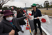 Volunteers hand out Japanese flags to well-wishers at the Imperial Palace to celebrate the 85th birthday of Emperor Akihito of Japan. The Emperor, who is the son of Japan's wartime leader, Emperor Hirohito, gave a speech to mark his last birthday before his upcoming abdication, saying he felt relief that his reign was coming to an end without having seen his country at war again and that it was important to continue to educate young people about japan's wartime past. Imperial Palace, Tokyo, Japan. Sunday December 23rd 2018