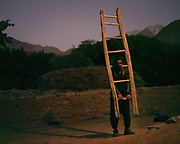 Man carrying hand made wooden ladder.  The traditional life of the Wakhi people, in the Wakhan corridor, amongst the Pamir mountains.