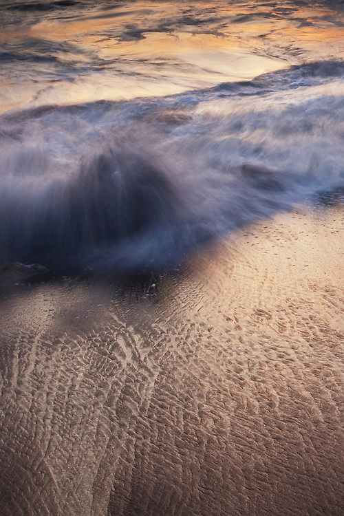 The crashing waves during sunset on a beach in northern California near Sausalito, California.
