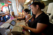"Lourdes Alvarez, restaurant owner and chef takes a phone order in her family's Mexican restaurant, Los Dos Laredos, in Chicago, Illinois while her daughter, Alejandra, checks her mobile phone after school. (From the book What I Eat: Around the World in 80 Diets.) The caloric value of her typical day's worth of food on a day in the month of September was 3,200 kcals. She is is 39; 5'2.5"" and 190 pounds. She grew up in an apartment above Los Dos Laredos, where she still helps out two days a week. Other days she spends long hours at her own restaurant in Alsip, Illinois. MODEL RELEASED."