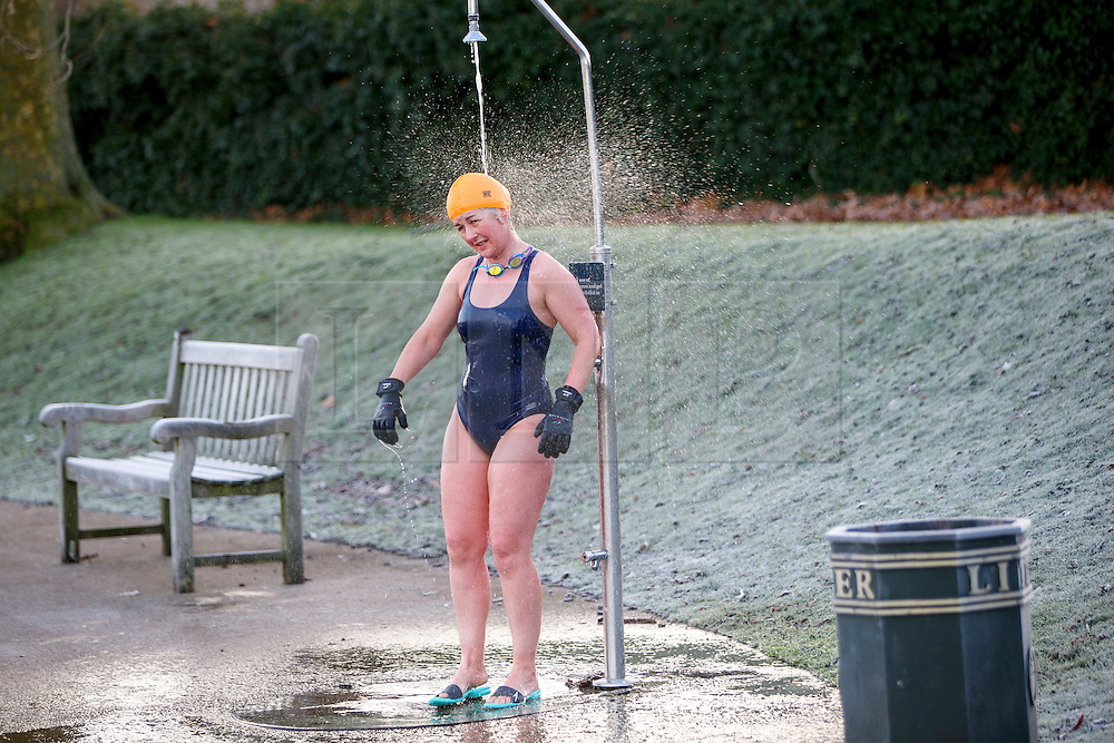© Licensed to London News Pictures. 03/01/2017. London, UK. A woman takes a shower after swimming in The Serpentine Lake in Hyde Park, London on a frosty morning as temperatures in the capital drop below zero celsius on Tuesday, 3 January 2017. Photo credit: Tolga Akmen/LNP