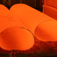 Large red hot steel tubes coming out of the rolling and forming mill