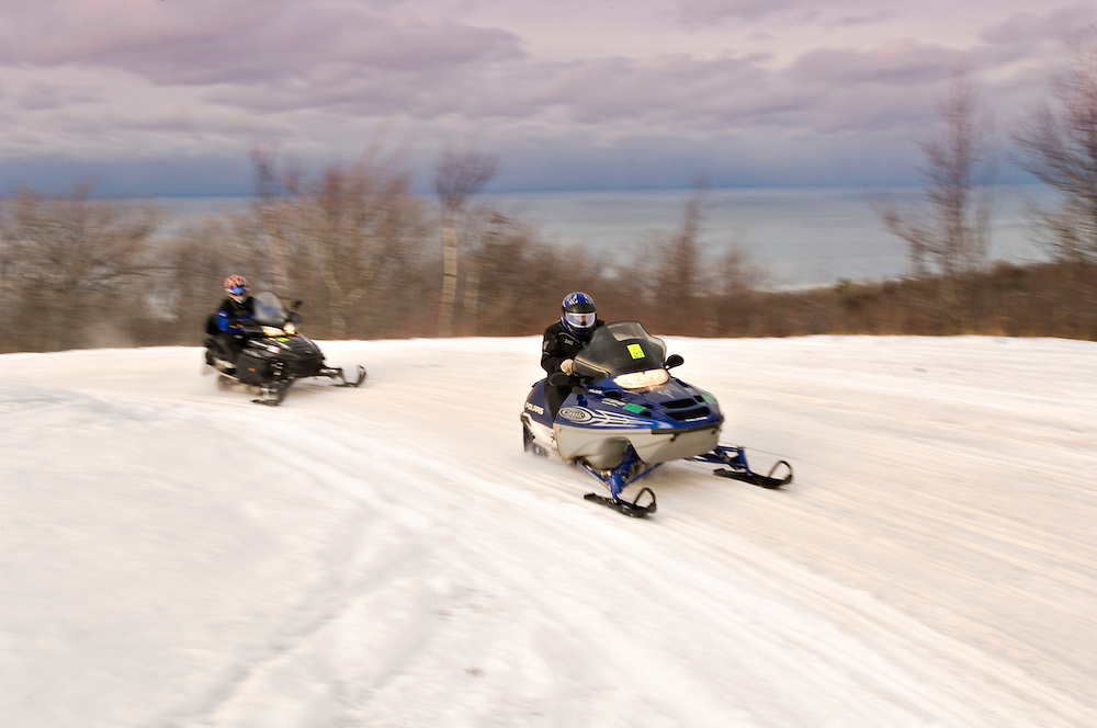 Snowmobilers near the top of Brockway Mountain near Copper Harbor Michigan with Lake Superior in the background.
