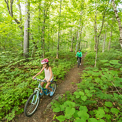 A girl and her mom ride mountain bikes on a trail near Deboullie Pond in Aroostook County, Maine. Deboullie Public Reserve Land.