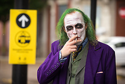© Licensed to London News Pictures . 26/07/2015 . Manchester , UK . The Joker having a cigarette in the rain outside the venue . Comic Con convention at Manchester Central Convention Centre . Photo credit : Joel Goodman/LNP
